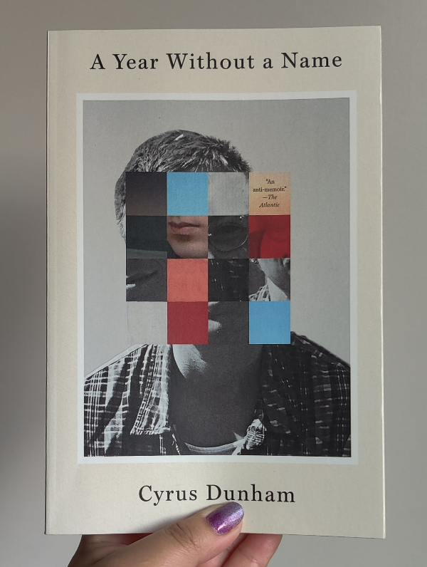 """A book on a white background. The cover of the book has the title at the top """"A Year Without a Name"""". There is the image of a person with squares superimposed on top of the face, which is also shifted so the top of the head doesn't align with the bottom. Each square has a different image or color, black square, blue square, grey square, a square with """"An anti-memoir"""" -- The Atlantic, squares with lips or eyes. It says Cyrus Dunham at the bottom."""