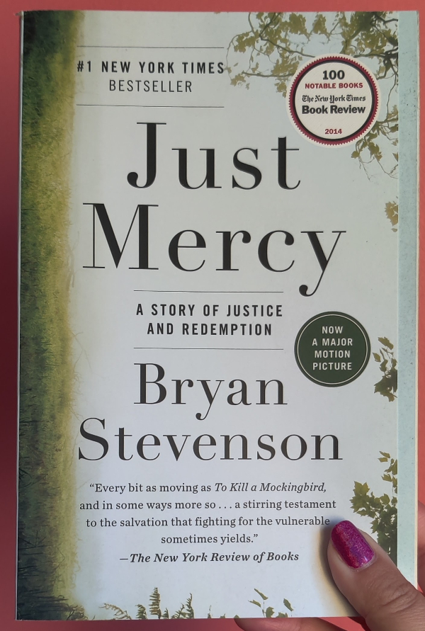 """An image of the book, titled Just Mercy in black letters. It says """"A Story of Justice and Redemption"""". The author's name is underneath """"Bryan Stevenson"""" A blurb is at the bottom and it says """"Every bit as moving as 'To Kill a Mockingbird', and in some ways more so...a stirring testament to the salvation that fighting for the vulnerable sometimes yields"""" by The New York Review of Books. The background image is that of grass with a misty or foggy day and branches coming down. The image is sideways so the grass is on the side of the spine of the book."""