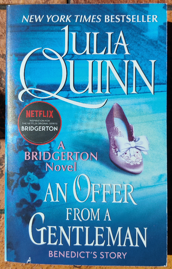 Cover of An Offer from a Gentleman by Julia Quinn. The background  is blue and features a pink shoe with a jeweled bow and clip.