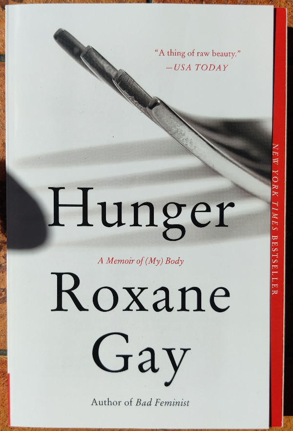 Cover of Hunger by Roxane Gay. The background is white and there is the prong end of a fork on the right casting a shadow on to the white background.