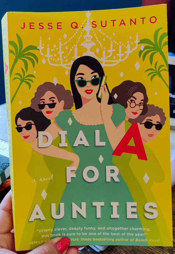 """Cover for """"Dial A for Aunties"""" The title is in white letters except for the A which is in bright red. There are 5 women depicted on the bright yellow cover, all wearing different shades of green. There is a white chandelier above them in the background as well as palm trees coming from the sides."""