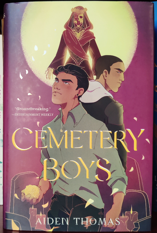 Cover of Cemetery Boys, featuring Yadriel at the front wearing a green shirt, Julian behind him facing the opposite direction, and Lady Death in the background facing straight at the viewer. A bright full moon is behind them all and marigold petals surround them.